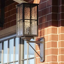 Large Scale Metro Lantern in Architectural Bronze finish, with Window Pane overlay and Waterfall art glass featured on a brick wall
