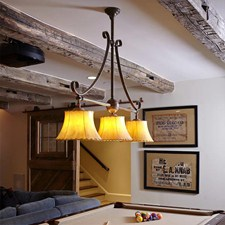 Shoreland Scroll Chandelier with sheepskin shades lights a billiards table.