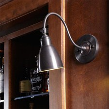 One Light Goose Neck Sconce with Articulated Metal Shade in Architectural Bronze lights a bar