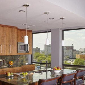 A trio of One Light Tribeca Pendants over top of an island in a modern condo kitchen.