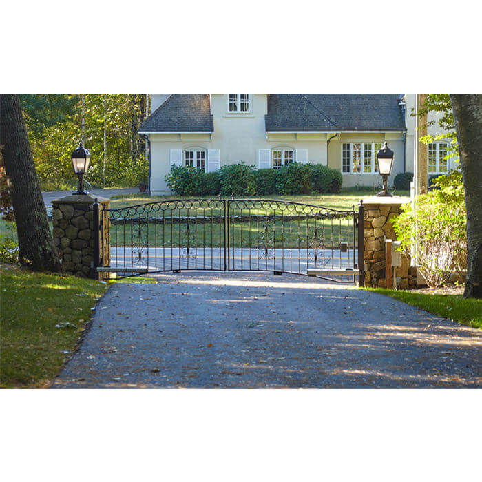 A Gated Driveway Entrance With Square Field Stone Columns Sets The Tone For  The Exterior Of The Elegant Mansard Style Home Featured In This Photo Shoot.